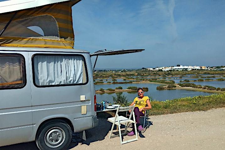 Bloggerin Sonja sitzt auf Campingstuhl neben ihrem Campervan